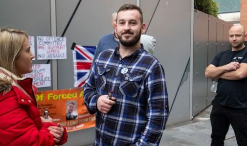 Protester James Goddard holds up sign as he is convicted of assaulting photographer