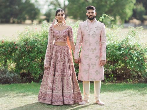 A bride and groom coordinated in stunning blush outfits at their wedding