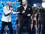 John Travolta sings on stage with rapper Pitbull while at Univision's Premio