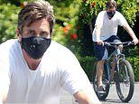 Christian Bale covers up in a black reusable face mask as he heads out for a solo bike ride
