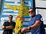 Joseph Baena and father Arnold Schwarzenegger stand next to mural of dad from his bodybuilding days