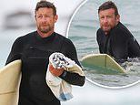 Simon Baker slips into a wetsuit and hits the beach for a surfing session with his sons in Sydney