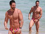 SAS Australia's James Magnussen shows off his muscular build in tiny Speedos as he hits the beach