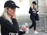 Mollie King displays her honed frame in black gym gear paired with a baseball cap