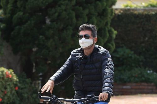 Simon Cowell not taking any chances as family wear face masks on bike ride