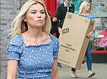 Georgia Toffolo flashes her toned tummy in a blue frilled top as she struggles with a large box