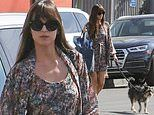 Dakota Johnson looks chic in a floral print mini dress and matching cover up while walking her dog