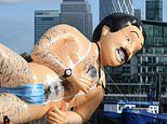 Worker ensures giant inflatable Borat is covered up as he floats down Thames to promote new movie