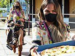Chrissy Teigen flashes serious leg as she treats photographers to fresh pizza after a studio visit
