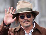Johnny Depp waves to fans as he leaves his Spanish hotel
