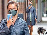 Helena Christensen covers up in a face masks and blue trench coat while out walking her dog in NYC