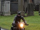 Batman sighted in Scotland: Caped crusader tears through a Glasgow cemetery on a motorbike