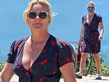 Jane Krakowski smiles in a delightful cherry print dress as she walks on the beach in the Hamptons