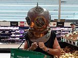 Shopper wears a DIVING HELMET while browsing for potatoes at a Woolworths supermarket