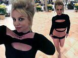 Britney Spears prances around in crop top and shorts as her Christmas tree sparkles in the distance