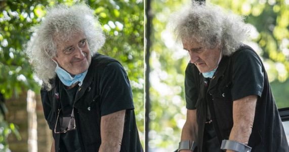 Brian May heads out on crutches after suffering heart attack and undergoing operation to install three stents