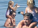 Leonardo DiCaprio puts a pint-sized family member on his shoulders as he takes a dip in the ocean