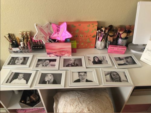 A woman decorated her makeup desk with framed screenshots of beauty YouTubers crying in their apology videos