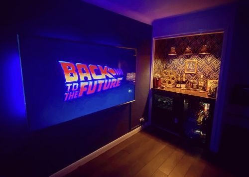 Film and TV prop man creates his own cinema at home with a minibar and drinks fridge, using old set pieces