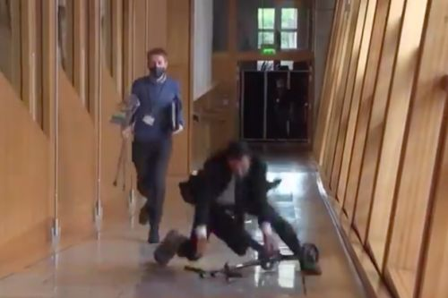 SNP Minister Humza Yousaf falls off knee scooter while riding in Scottish Parliament