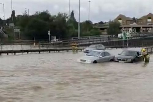 Drivers rescued from cars as burst water main floods road