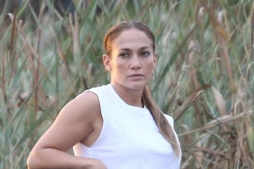 Jennifer Lopez stuns in a crop top and leggings as she meditates on the beach