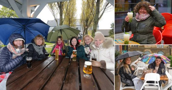 Brits enjoy pints huddled under umbrellas as they brave pubs in torrential rain