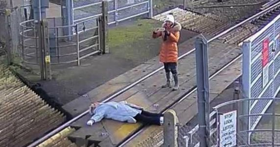 Woman lies down on tracks at railway crossing so she can pose for photo