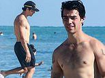 Joe Jonas shows off his buff body as he catches rays shirtless during beach day
