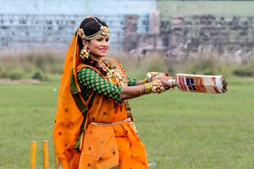 Bangladeshi cricketer bats a six on the field wearing traditional wedding attire
