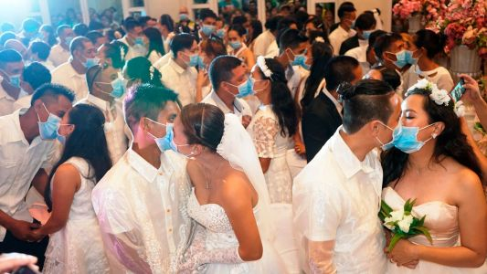 Newlyweds kiss through coronavirus masks in mass wedding in Philippines