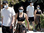 Charli XCX flashes her abs in a black crop top and leggings