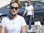 Olivia Wilde dons a casual look in a plain white tee and blue leggings while walking her dog