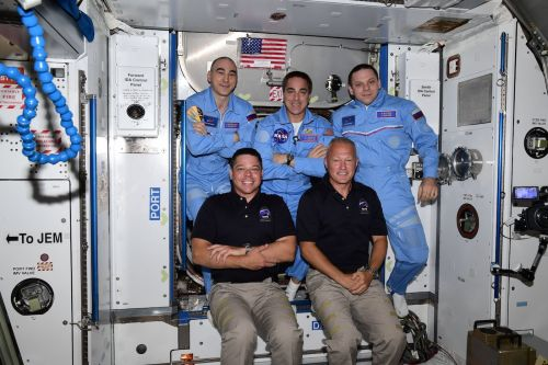 Making history, astronauts ride commercial capsule to space station
