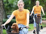 Devon Windsor shows her support for gun control as she rocks orange shirt during bike ride with dog