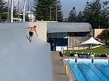 Daredevil cheats death by jumping headfirst off a roof and into a pool