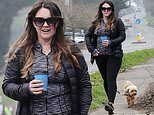 Lacey Turner nurses a coffee as she steps out for a brisk walk with pet dog Ned