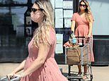 April Love Geary chooses a pink empire waist dress as she makes an early morning grocery run