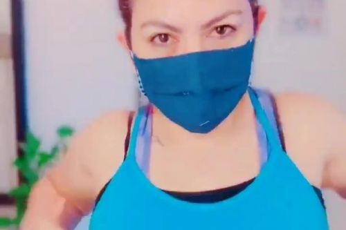 Woman demonstrates correct way to wear face covering by comparing it to her bra