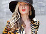 Caprice goes braless under bold tiger print suit