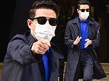 Masked Rami Malek cuts a dapper figure in a black trench coat as he attends No Time To Die promotion