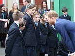 Prince Harry is greeted by school children taking part in a tree planting project