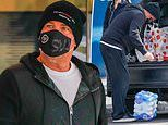 Shane Warne drops a case of water onto his foot while loading groceries into his car