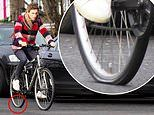 Eddie Redmayne cuts a casual figure in a red shirt but looks unimpressed as his bike gets flat tyre