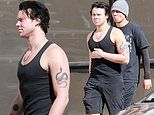 5SOS's Ashton Irwin flaunts his bulging biceps and tattoos wearing a black tank top with Calum Hood