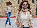 Cindy Crawford, 55, cuts casual figure in white top and blue jeans while running errands in Malibu