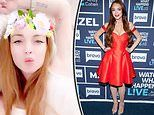 Lindsay Lohan pouts for the camera as she blows kisses to fans from her Sydney bed