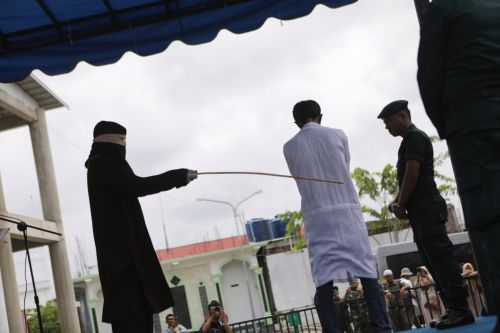 Men publicly caned after being accused of gambling in Indonesia