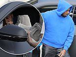 Kanye West happily signs a fan's pair of Adidas Yeezy shoes while arriving at his Calabasas office