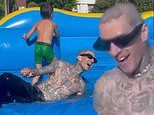 Travis Barker drifts down water slide on Palm Springs holiday with Kourtney Kardashian and her kids